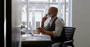 Homem de negócios que come o café ao falar na linha terrestre e ao usar o portátil na mesa 4k vídeos de arquivo