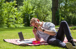 Homem de negócios que come o sanduíche e que fala no telefone Fotografia de Stock Royalty Free