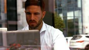Homem de negócios que come um café do od do copo ao usar o portátil vídeos de arquivo