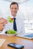 Homem de negócios que come uma salada Fotos de Stock Royalty Free