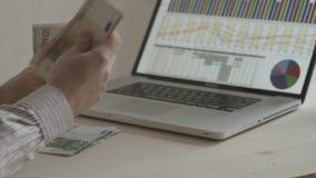 Homem de negócios que conta euro- contas na frente do caderno