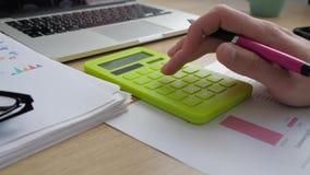 Homem de negócios que conta na calculadora O homem de negócios que analisa o mercado e considera na calculadora o tamanho de video estoque