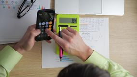 Homem de negócios que conta na calculadora O homem de negócios que analisa o mercado e considera na calculadora o tamanho de vídeos de arquivo