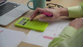 Homem de negócios que conta na calculadora O homem de negócios que analisa o mercado e considera na calculadora o tamanho de filme