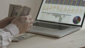 Homem de negócios que conta notas de dólar na frente do caderno filme