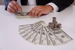 Homem de negócios que conta o dinheiro com moedas e o dinheiro sobre a mesa fotografia de stock