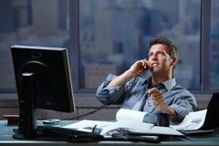 Homem de negócios que convida a linha terrestre no escritório Imagens de Stock