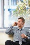 Homem de negócios que convida o sofá com gesto Imagens de Stock Royalty Free