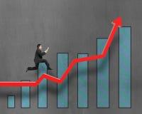 Homem de negócios que corre na seta vermelha do crescimento com carta foto de stock royalty free