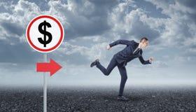 Homem de negócios que corre no sinal do asfalto e de estrada com dólar imagem de stock