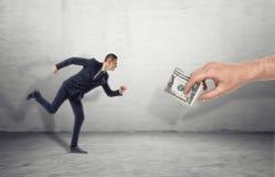 Homem de negócios que corre para a mão grande do homem que seduz com nota de dólar fotografia de stock royalty free