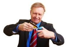 Homem de negócios que corta seu cartão de crédito Fotos de Stock Royalty Free