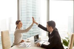 Homem de negócios que dá a elevação cinco da mulher de negócios no escritório, lado da cidade imagem de stock