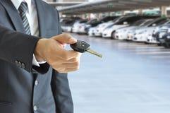 Homem de negócios que dá uma chave do carro - venda do carro & conceito do arrendamento Imagens de Stock