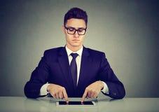 Homem de negócios que datilografa com os dedos em seu tablet pc imagem de stock