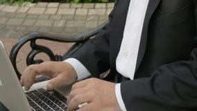 Homem de negócios que datilografa em um portátil e que senta-se em um banco na rua vídeos de arquivo
