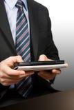 Homem de negócios com dispositivo da toque-tela Fotografia de Stock Royalty Free