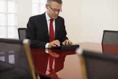 Homem de negócios que datilografa no computador da almofada de toque imagem de stock