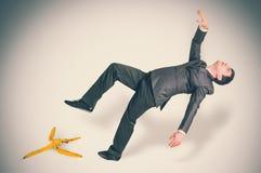 Homem de negócios que desliza e que cai de uma casca da banana fotos de stock