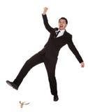 Homem de negócios que desliza na casca da banana Fotografia de Stock Royalty Free