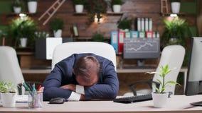 Homem de negócios que dorme com sua cabeça na mesa video estoque