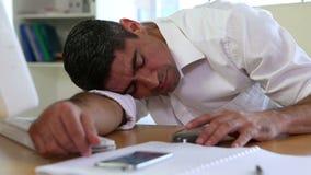 Homem de negócios que dorme em sua mesa video estoque