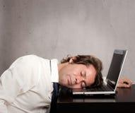 Homem de negócios que dorme no portátil fotografia de stock royalty free