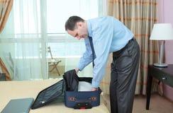 Homem de negócios que embala uma mala de viagem Imagens de Stock Royalty Free