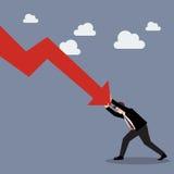 Homem de negócios que empurra duramente contra o gráfico de queda para baixo Foto de Stock Royalty Free