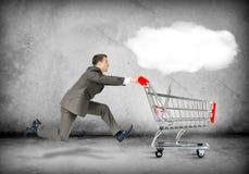 Homem de negócios que empurra o carrinho de compras Fotografia de Stock Royalty Free