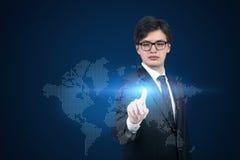 Homem de negócios que empurra o mapa do mundo Fotografia de Stock