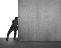 Homem de negócios que empurra o muro de cimento afastado imagens de stock royalty free