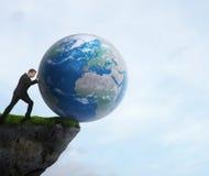 Homem de negócios que empurra a terra do planeta fora de um penhasco Imagem de Stock Royalty Free