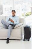 Homem de negócios que envia um texto que senta-se no sofá que espera para partir na viagem de negócios Fotografia de Stock