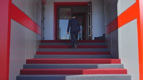 Homem de negócios que escala acima as escadas no prédio de escritórios filme