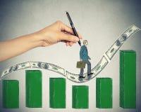Homem de negócios que escala acima na carta crescente do monte das notas de dólar do dinheiro Foto de Stock