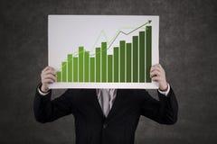 Homem de negócios que esconde atrás do gráfico Imagem de Stock Royalty Free