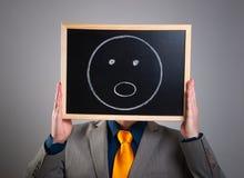 Homem de negócios que esconde sua cara com um quadro de avisos branco com um surpri Imagem de Stock Royalty Free