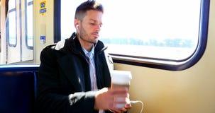 Homem de negócios que escuta a música ao comer o café vídeos de arquivo