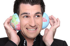 Homem de negócios que escuta o globo foto de stock