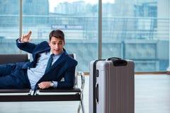 Homem de negócios que espera no aeroporto por seu plano no cla do negócio imagem de stock royalty free