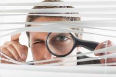 Homem de negócios que espreita através das cortinas com lupa imagens de stock royalty free