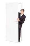 Homem de negócios que espreita através de uma porta aberta Imagem de Stock Royalty Free