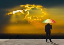 Homem de negócios que está atrás com guarda-chuva multicolorido Fotos de Stock Royalty Free