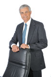 Homem de negócios que está atrás de sua cadeira imagem de stock royalty free