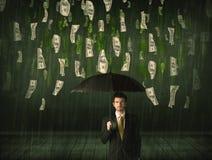 Homem de negócios que está com o guarda-chuva no conceito da chuva da nota de dólar Fotografia de Stock Royalty Free
