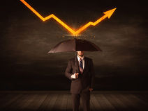Homem de negócios que está com o guarda-chuva que mantém a seta alaranjada Fotografia de Stock