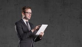 Homem de negócios que está com tabuleta do computador em um fundo escuro Fotos de Stock