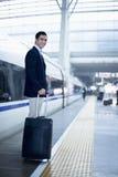 Homem de negócios que está com uma mala de viagem na plataforma da estrada de ferro por um trem de alta velocidade no Pequim imagem de stock royalty free