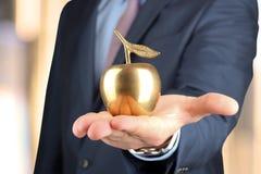 Homem de negócios que está e que guarda a maçã dourada em sua mão Imagem de Stock Royalty Free
